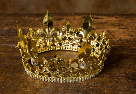 41303849 - medieval style golden crown on antique wooden background